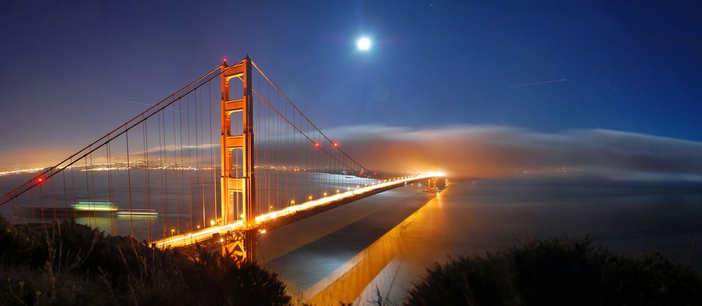 Golden Gate Bridge with full moon and milky clouds