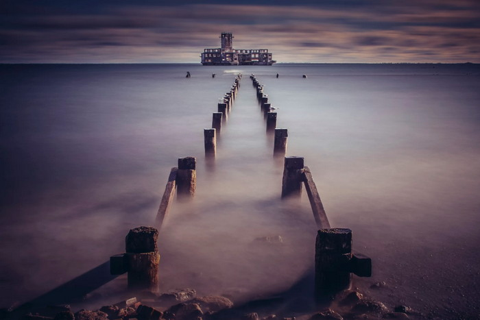 long exposure shot of an historical place with misty waters and neutral colors