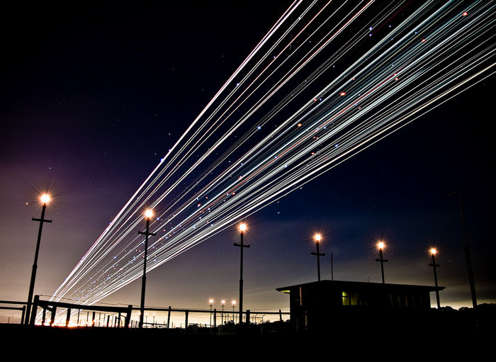 airplane landing shot with sparkling trails of light