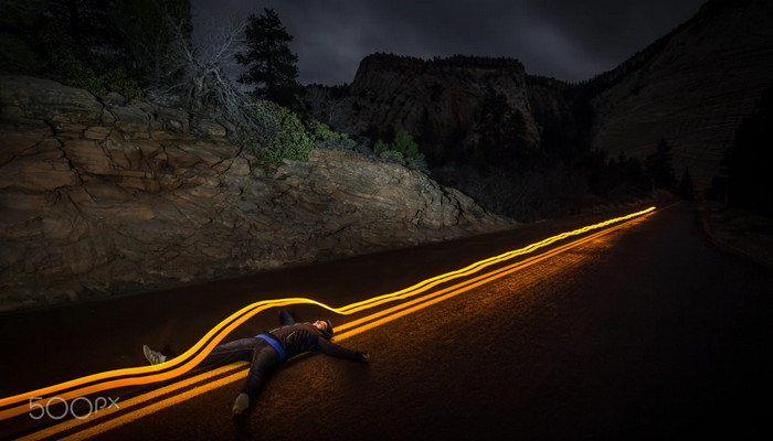 person lying on the road at night with light trails effect