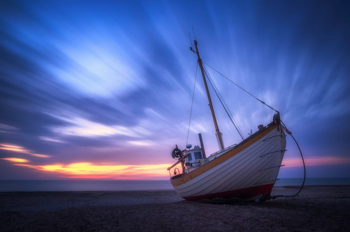 a great composition of a boat and sunset sky